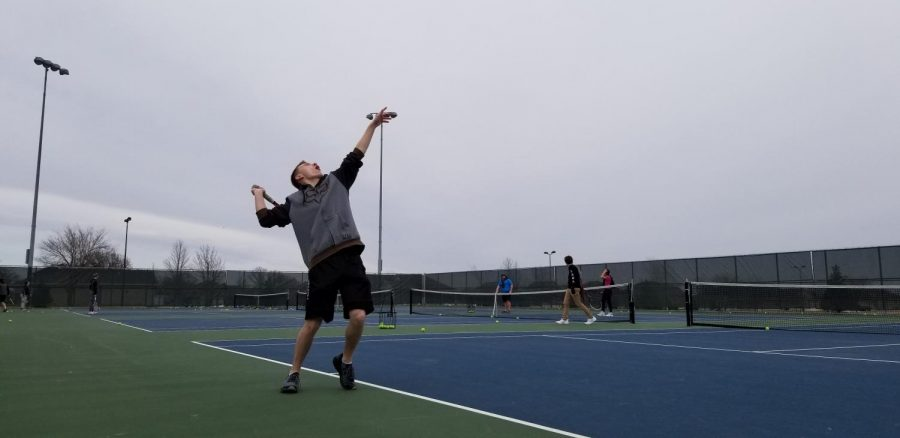 Justin Shapekahm serves it up on the tennis courts.