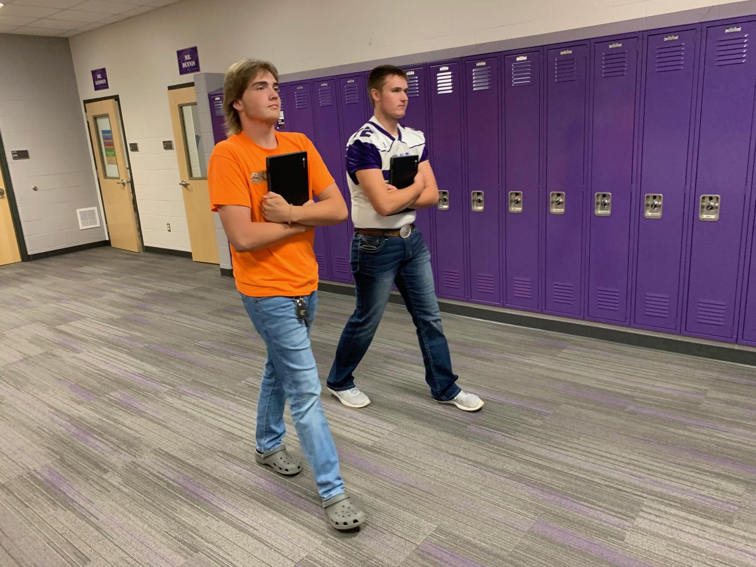 Two of New Ulm's high school students take a stroll down the hallway with the new Chromebooks in hand.