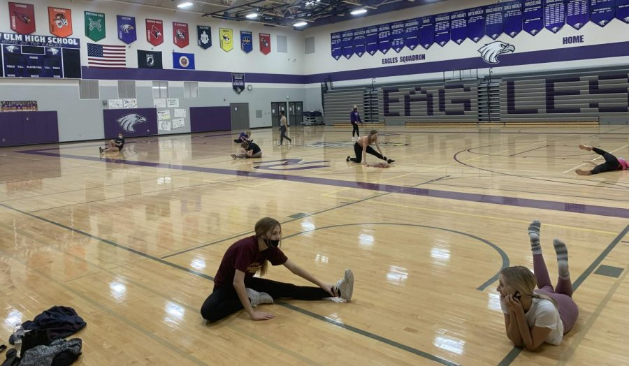 Varsity kick dancers social distance while stretching.