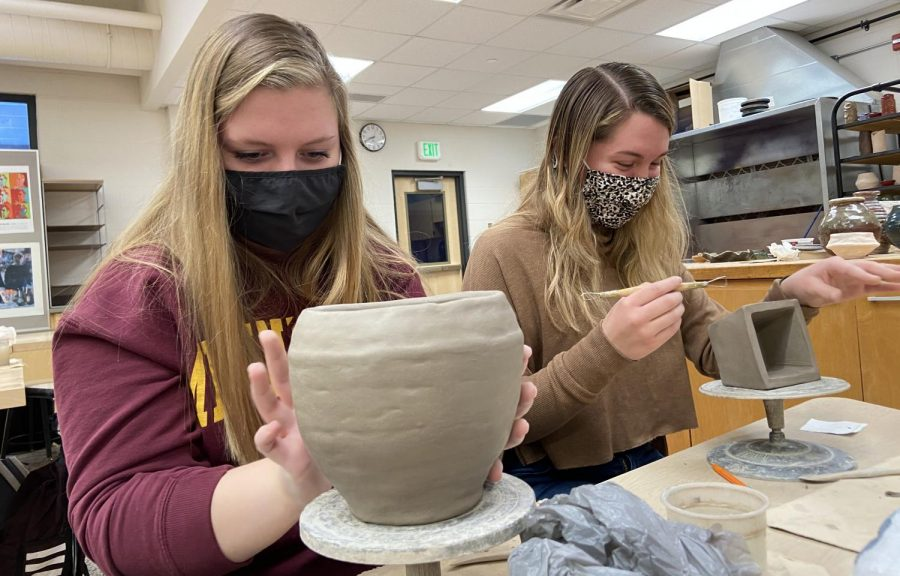 Senior students Abby Bianchi and RyAnn Miller working hard on their coil pots.